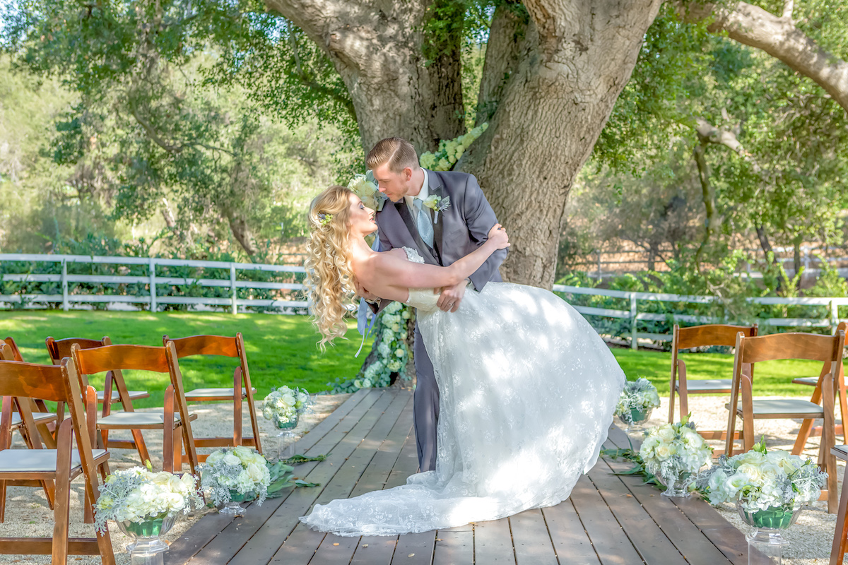 150 year old oak tree, draped with white roses, groom dipping the bride for a kiss